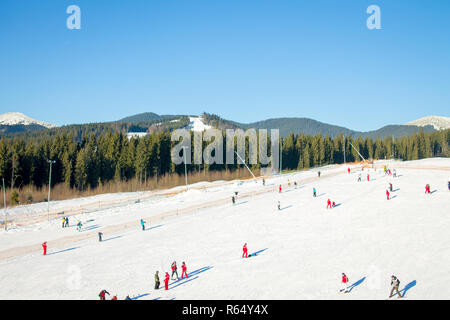 Bukovel ski resort in Carpathian mountains in winter. People skiing on slope - Stock Photo