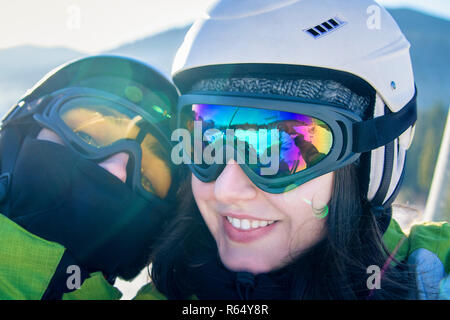 Portrait of young couple riding on chairlift on ski resort. Happy people wearing ski helmets and taking selfie - Stock Photo