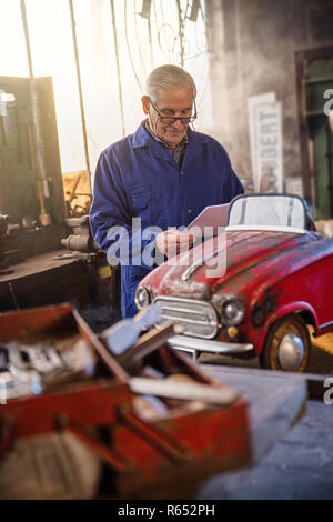 Senior man in his workshop repairing an old fashioned pedal car  - Stock Photo