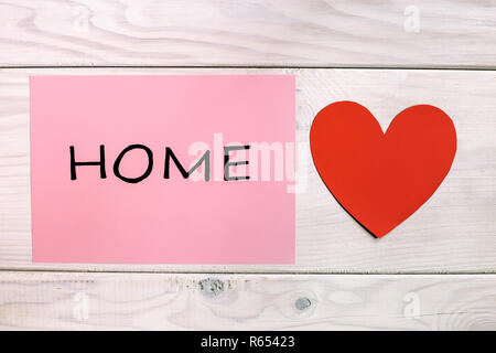 Word home sweet home with heart shape on wooden table - Stock Photo