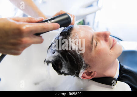 Profile view of a young man getting his hair washed and his head massaged in a hair salon. - Stock Photo