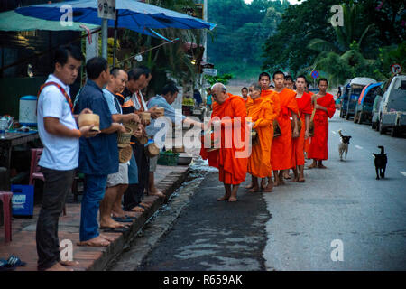 Tak bat ritual - Buddhist monks receive rice and food from pupulation in early morning in Luang Prabang , Laos, Asia - Stock Photo