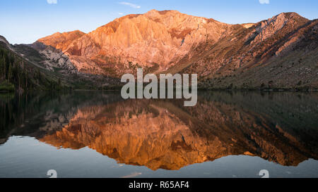 Panorama of the golden light of sunrise on mountain peaks reflected in the calm waters of Convict Lake in the Sierra Nevada mountains of California - Stock Photo