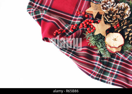 Christmas festive styled composition. Winter floral arrangement. Pine cones, fir tree branches, red holly berries and wooden stars and on checkered tartan plaid. White table background. Flat lay, top - Stock Photo