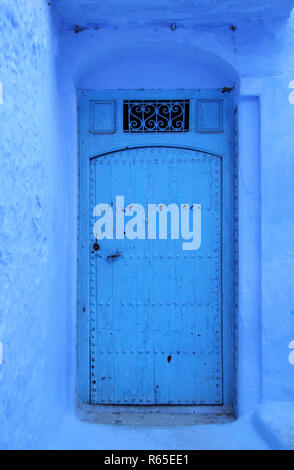 Traditional powder blue painted house facade and studded wooden door in the historical Medina of Chefchaouen, Morocco. - Stock Photo