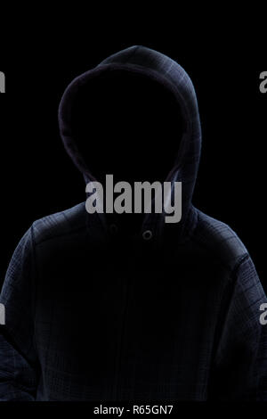 An anonymous backlit mysterious man wearing hoodie in silhouette isolated on black background. Concept of a criminal or spooky evil stalking in the sh - Stock Photo