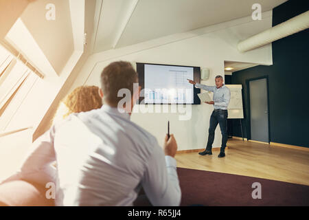 Businesspeople sitting together in an office asking their manager questions during a graph presentation on a monitor - Stock Photo
