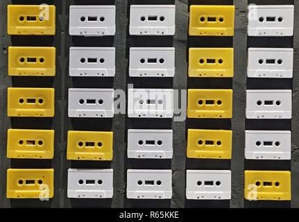 Wall decorated with white several music tapes - Stock Photo