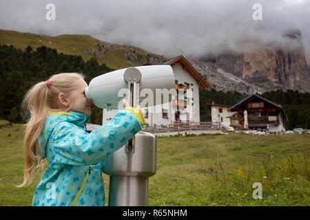 Little girl looks through binoculars in the mountains Dolomites, Italy - Stock Photo