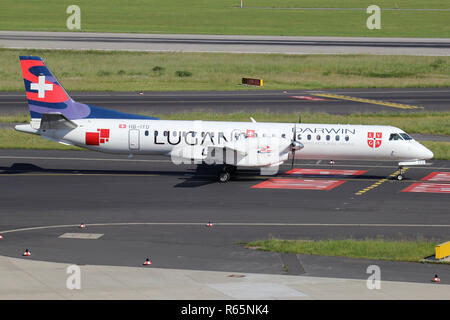 Swiss Darwin Saab 2000 in special Lugano livery with registration HB-IYD on taxiway of Dusseldorf Airport. - Stock Photo