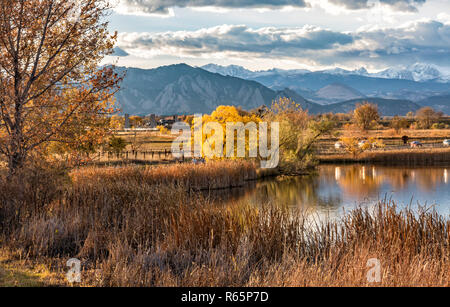 The Flatirons and Front Range of the Rocky Mountains Reflected in Stearns Lake in Autumn in Broomfield, Colorado - Stock Photo