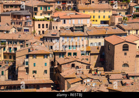 Rooftop view of old stone, stucco, and brick buildings with colorful window shutters in a dense urban cityscape in the medieval city of Siena, Italy - Stock Photo