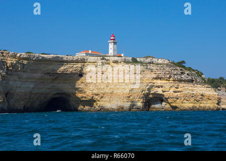 A view of Alfanzina Lighthouse above the rugged limestone cliffs and grottos along the Algarve coast in Portugal. - Stock Photo