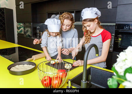 Happy family in kitchen. Mother and two children preparing dough, bake apple pie. Mom and daughters cooking healthy food at home and having fun. House - Stock Photo