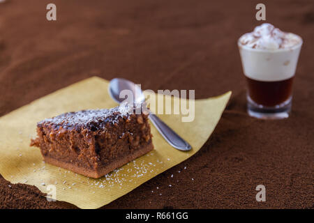 Little cup of piccolo latte macchiato on a table covered with ground coffee as a background and chocolate brownie with cocoa cream and coconut chips