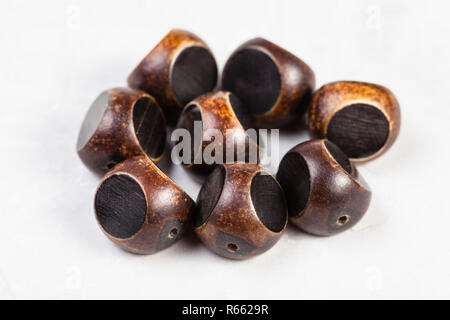 brown beads carved from natural horn on gray - Stock Photo
