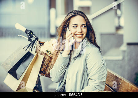 Happy young woman talking on mobile phone while sitting on the bench in the city Stock Photo
