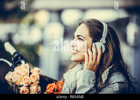 Happy young woman listening music in headphones while sitting on the bench in the city - Stock Photo