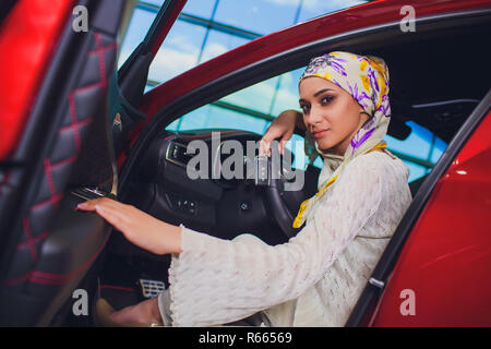 property and people concept - muslim woman in hijab with car key over car show background. happy woman taking car key from dealer in auto show or salon - Stock Photo