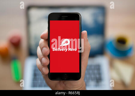 A man looks at his iPhone which displays the Delivery Hero logo, while sat at his computer desk (Editorial use only). - Stock Photo