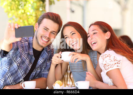 Three smiley friends taking selfies with a smart phone sitting in a coffee shop - Stock Photo
