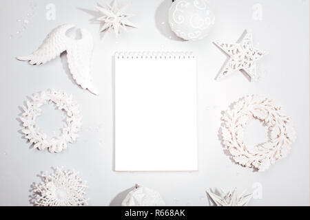 White square notebook among Christmas decorative toys on grey background. Flat lay style. Planning concept. - Stock Photo