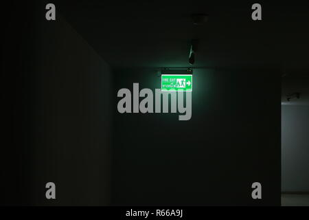 lighting from fire exit sign in the dark corridor of a building - Stock Photo