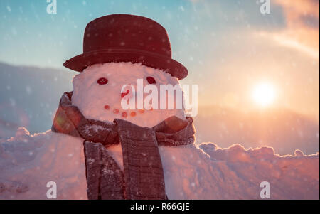 Photo of a cute snowman dressed in a stylish hat and scarf in a snowy frosty evening on a sunset background, happy winter holidays tradition