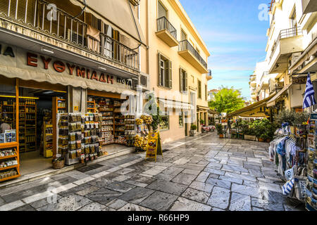 Shops, souvenir stands, markets and cafes line the narrow medieval roads in the touristy Plaka district in the ancient city of Athens, Greece. - Stock Photo