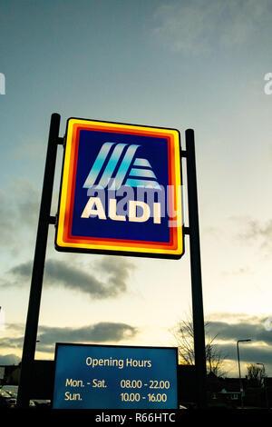 Opening hours on an illuminated Aldi Sign at dusk in Dinnington, Rotherham UK