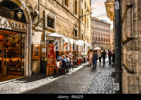 Tourists and local Italians enjoy afternoon shopping and dining at a sidewalk cafe patio on a narrow side street in the historic center of Rome Italy - Stock Photo