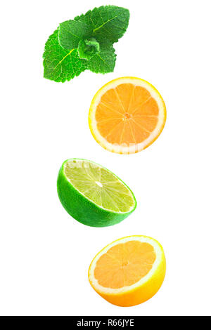Falling pieces of mint, lemon and lime isolated on white - Stock Photo