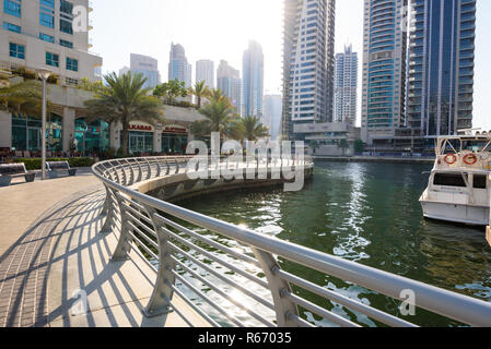 Dubai, United Arab Emirates - July 25 2018: A view of the bridge and walk way at Dubai Marina, showing various stores, boats and skyscrapers - Stock Photo