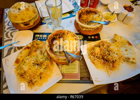 Dubai, United Arab Emirates - July 2018: Table Top view showing various dishes of fresh Biryani served in restaurant in Dubai - Stock Photo