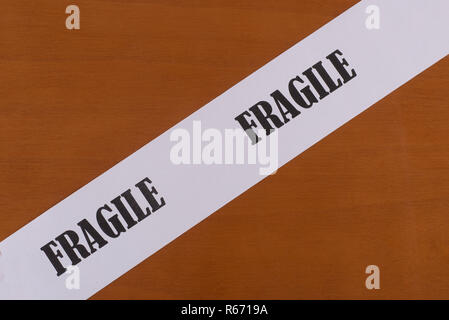 strip of paper with the word fragile diagonally - Stock Photo