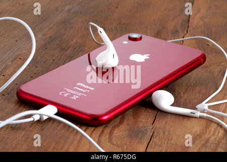 Koszalin, Poland – December 04, 2018: Red iPhone XR on a wooden table with white earphones. The iPhone XR is smart phone with multi touch screen produ - Stock Photo