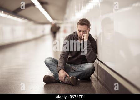 Sad young man crying suffering depression stress sitting on ground street subway tunnel looking desperate leaning on wall alone in Mental disorder Emo