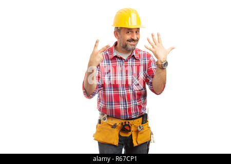 Cheerful constructor holding up fingers as number seven concept isolated on white studio background - Stock Photo