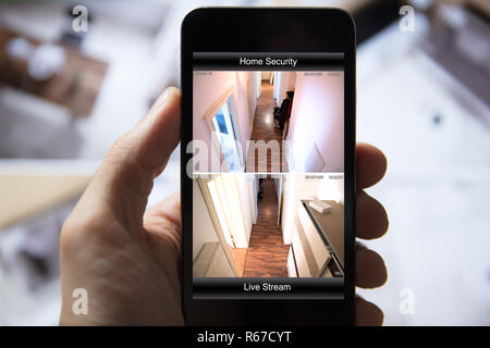 Person Using Home Security System On Mobile Phone - Stock Photo