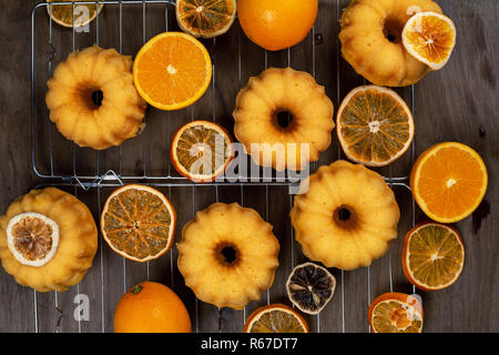 Small orange bundt cakes with fresh and dry oranges on cooling ruck, top view, flat lay, horizontal composition - Stock Photo