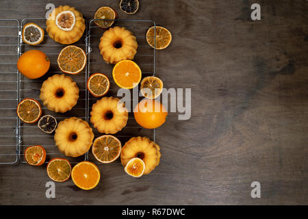 Small orange Bundt cakes with fresh and dry oranges on cooling ruck, top view, flat lay, copy space - Stock Photo