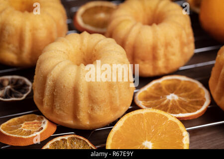 Small orange bundt cakes with fresh and dry oranges on cooling ruck, close up - Stock Photo
