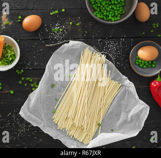 Raw ingredients for cooking vegetarian udon noodles on dark wooden table in home kitchen top view - Stock Photo