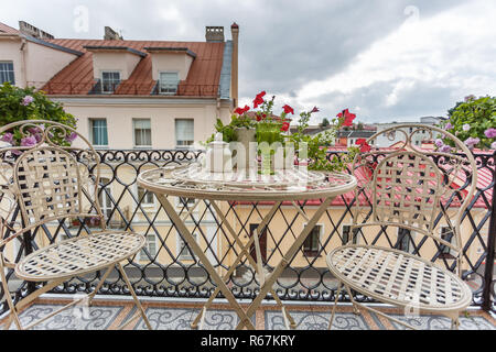 view from the room to the balcony with summer furniture and the old city on the background - Stock Photo