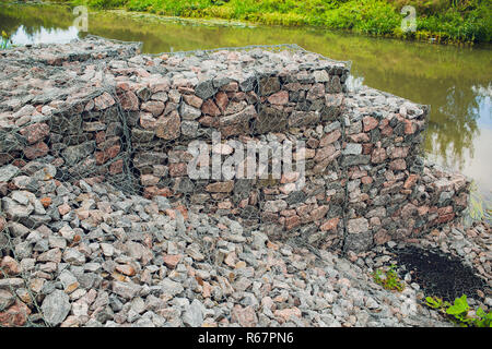 Texture for the background backdrop freely lying stone supported by a metal mesh. Technology of construction of fences from natural materials. Element of landscape design for architecture - Stock Photo