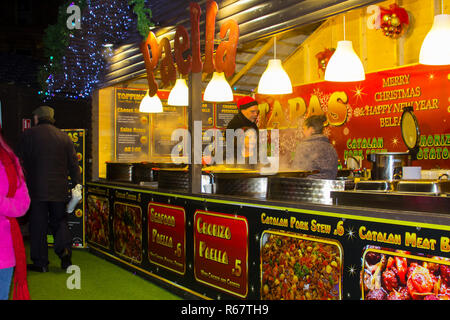 30 November 2018 A busy food stall selling Spanish dishes at the Belfast Christmas Fair located in a wooden booth in the grounds of Belfast City Hall. - Stock Photo