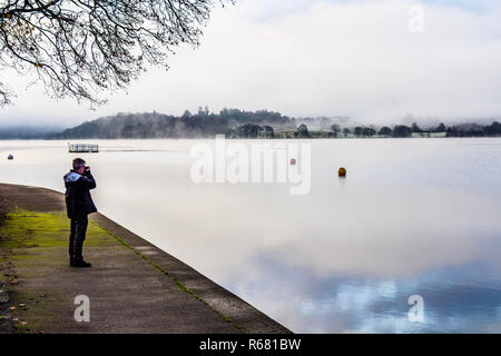 A man taking a photo of Windermere on a cold and frosty winter morning with low mist in the Lake District. Waterhead, Ambleside, Cumbria, UK. December 2018. - Stock Photo