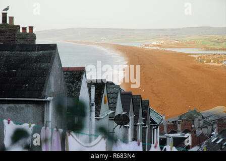 Portland, Dorset, UK. 4th December 2018. Fortuneswell cottages slope down to Chesil Beach, bathed in early-morning sunshine Credit: stuart fretwell/Alamy Live News - Stock Photo