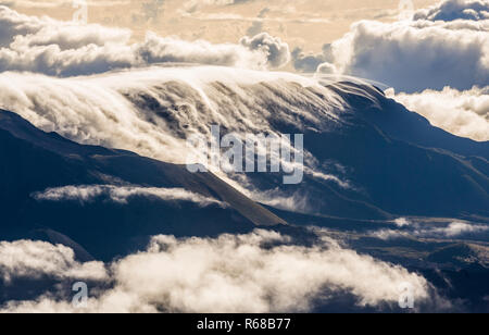 Clouds flowing over Haleakala crater and surrounding mountains as seen from atop Haleakala, Maui, Hawaii, USA. - Stock Photo