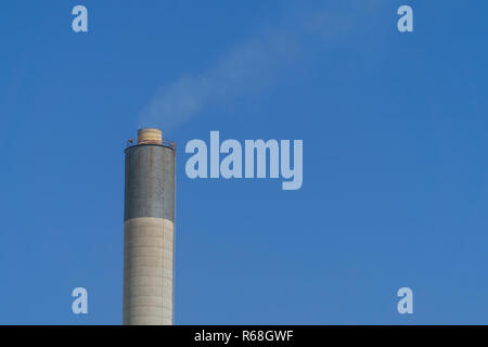 Industrial Chimney and smoke with blue sky background. - Stock Photo